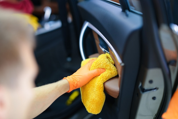 Mann in gummihandschuhen wischt staub von der autotür mit mikrofasertuch nahaufnahme