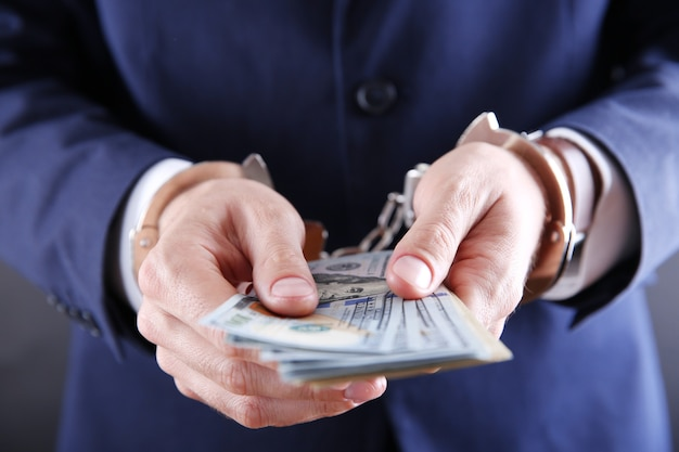 Mann in handschellen, der dollar-banknoten zählt, nahaufnahme