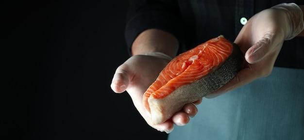 Mann in handschuhen hält lachsfleisch auf dunkler oberfläche
