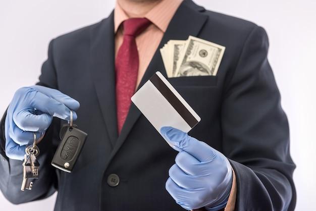 Mann in handschuhen halten kreditkarte und autohausschlüssel für sicherheitsabkommen verkauf oder miete. covid19