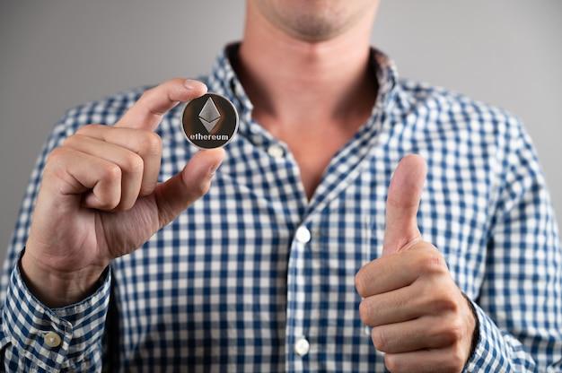 Mann in hemdkrawatte mit ethereum-münzen-kryptowährung zeigt daumen nach oben. der preis der kryptowährung ethereum steigt.