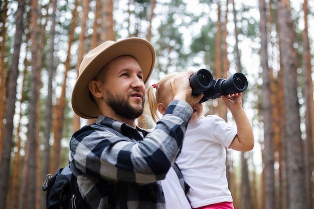 Mann in hut und rucksack und kind schauen durch fernglas beim wandern im wald. familienwanderung in die berge oder in den wald.