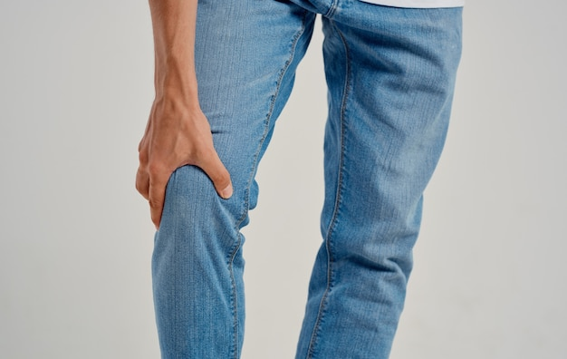 Mann in jeans berührt sein knie mit seinen händen auf einem hellen hintergrund beschnittene ansicht. hochwertiges foto