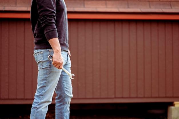 Mann in jeans hält einen schraubenschlüssel