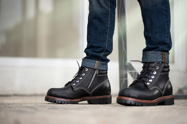 Mann in jeans und schwarzen lederstiefeln