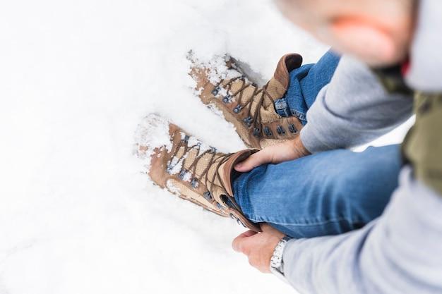Mann in jeans und stiefeln auf schnee