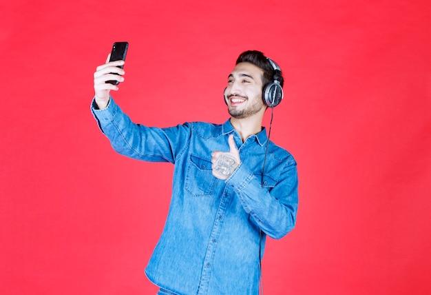 Mann in jeanshemd mit kopfhörern, der sein selfie macht oder einen videoanruf tätigt.