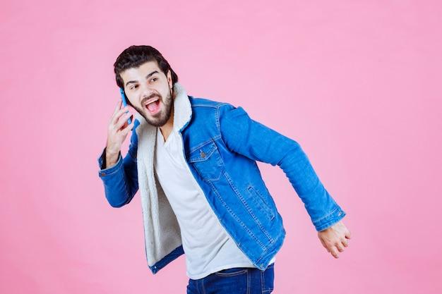 Mann in jeansjacke, der mit dem handy spricht.
