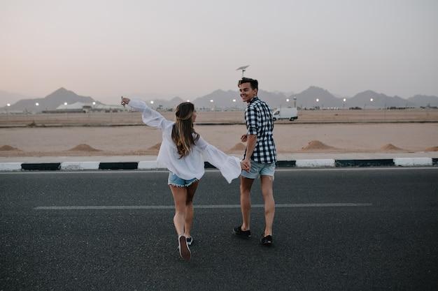 Mann in jeansshorts und langhaarige frau in trendiger bluse läuft über die straße und genießt bergblick. lachendes junges paar, das hände hält, die auf autobahn gehen und spaß draußen im sommer haben
