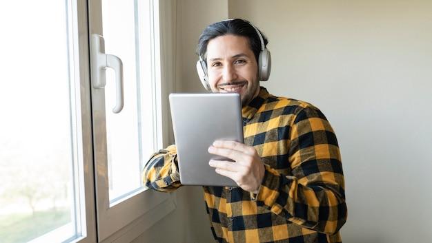 Mann in kariertem hemd, der sich mit einem tablet in der hand an ein fenster lehnt, während er musik hört