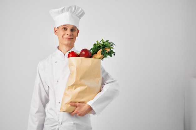 Mann in kochuniform food-service-paket lebensmittelzubereitung gesund. foto in hoher qualität