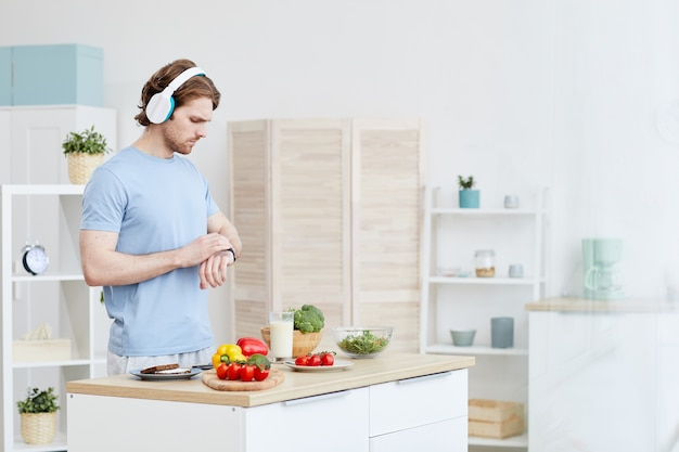 Mann in kopfhörern, der die zeit auf seiner uhr überprüft, während er in der häuslichen küche steht. er wird abendessen machen