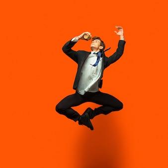 Mann in lässiger büroartkleidung, die auf leuchtendem orange lokalisiert springt und tanzt