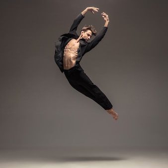 Mann in lässiger büroartkleidung, die lokalisiert auf grau springt und tanzt