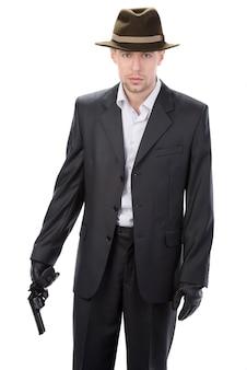 Mann in lederhandschuhen und anzug und waffe.