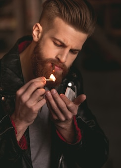 Mann in lederjacke zündet sich eine zigarette an.
