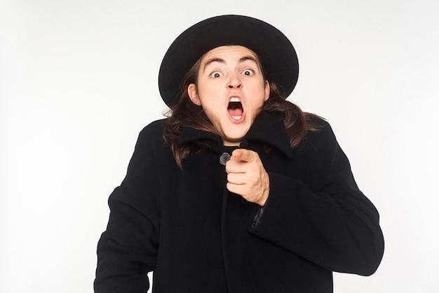 Mann in mantel und hut mit offenem mund und zeigt mit den fingern auf die kamera. studioaufnahme, isoliert auf weißem hintergrund