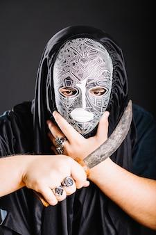 Mann in maske mit dolch
