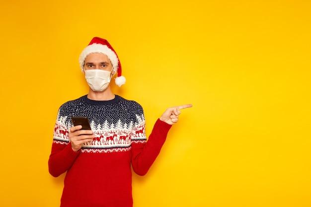 Mann in maske weihnachtspullover weihnachtsmütze mit telefon in den händen zeigt auf einen leeren bereich für werbung