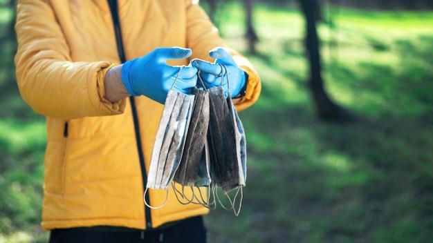 Mann in medizinischen handschuhen, die einen haufen schmutziger medizinischer masken halten, die vom boden erhoben werden