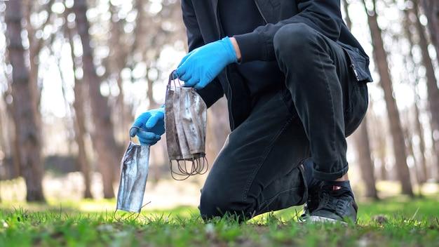 Mann in medizinischen handschuhen, die schmutzige medizinische masken vom boden in einem park aufheben