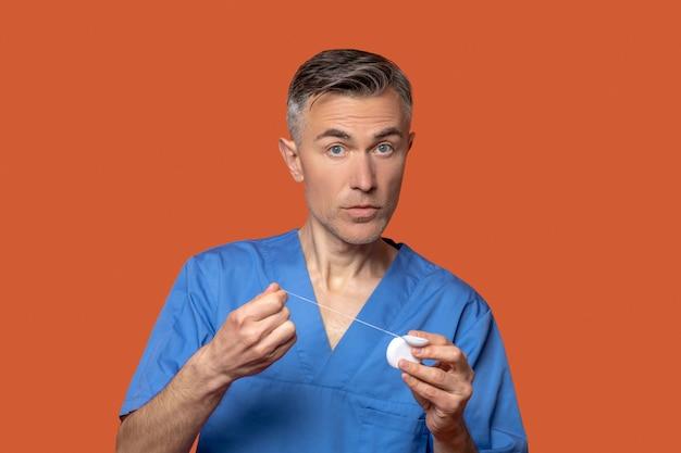 Mann in medizinischer kleidung mit zahnseide in den händen