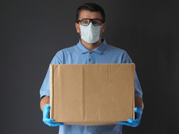 Mann in medizinischer maske und handschuhen lieferte das paket. kurier mit einem karton. paketzustelldienst während des epidemischen pandemie-coronavirus 2019-ncov, covid-19-virus.