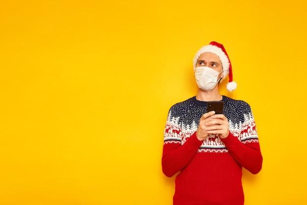 Mann in medizinischer maske weihnachtspullover weihnachtsmütze hält smartphone in den händen schreibt nachricht
