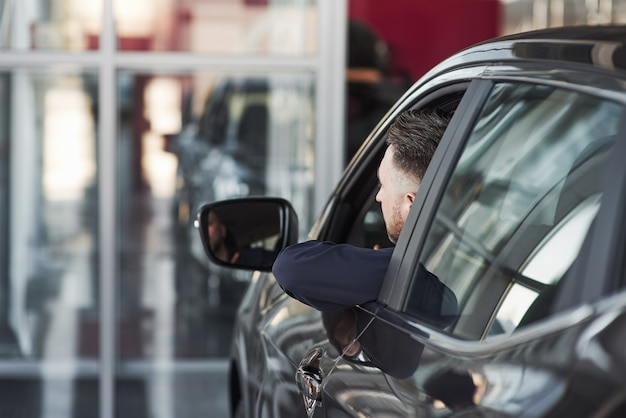 Mann in offizieller kleidung, der sein neues auto im autosalon versucht