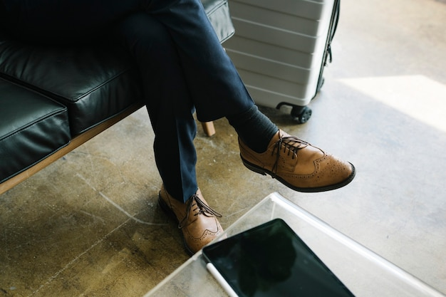 Mann in oxford-schuhen sitzt auf einer couch neben einem gepäck