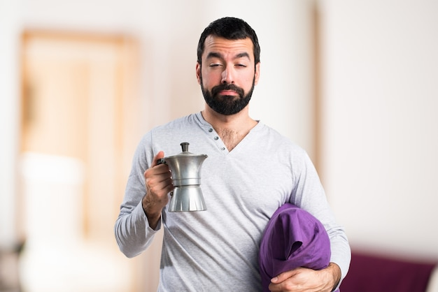 Mann in pyjama mit einer kaffeekanne