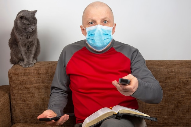 Mann in quarantäne zu hause mit einer medizinischen maske im gesicht