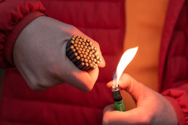 Mann in red jacked beleuchtet viele kleine schwarze feuerwerkskörper in seiner hand mit gasfeuerzeug.