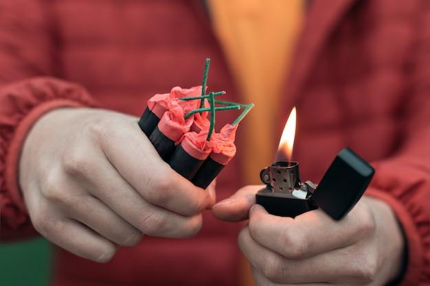 Mann in red jacked, der mehrere feuerwerkskörper in seiner hand mit benzinfeuerzeug beleuchtet.