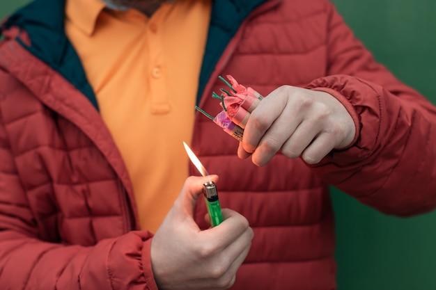 Mann in red jacked, der mehrere feuerwerkskörper in seiner hand mit gasfeuerzeug beleuchtet.
