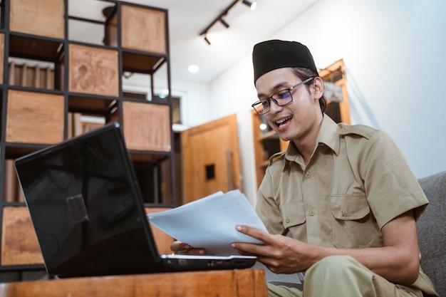 Mann in regierungsuniform, der papiere hält, während er von zu hause aus online mit einem laptop arbeitet