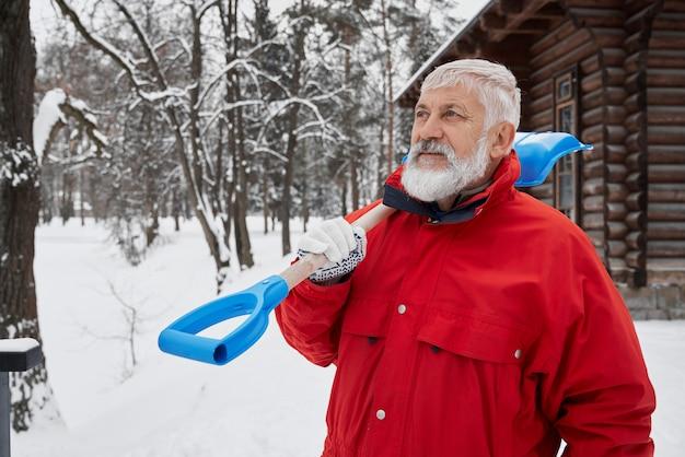 Mann in roter jacke mit schneeschaufel auf der schulter.