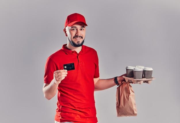 Mann in roter mütze, t-shirt, die fast-food-bestellung auf grauem hintergrund isoliert. männlicher kurier mit kreditkarte, papierpaket mit essen, kaffee. produktlieferung vom geschäft oder restaurant nach hause