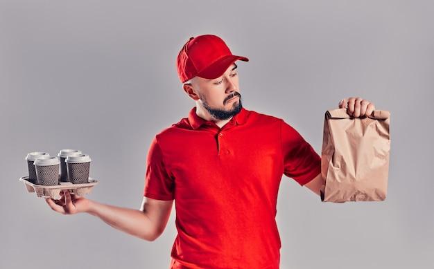 Mann in roter mütze, t-shirt, die fast-food-bestellung auf grauem hintergrund isoliert. männlicher mitarbeiterkurier halten papierpaket mit essen, kaffee. lieferung der produkte vom geschäft oder restaurant nach hause. platz kopieren
