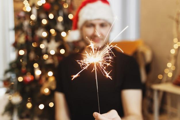 Mann in roter weihnachtsmütze mit weihnachts- oder neujahrswunderlichtern