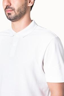 Mann in schlichtem weißem poloshirt bekleidung studioshooting