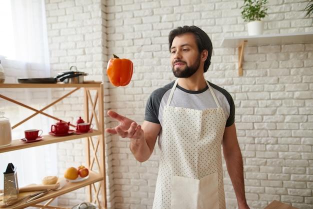 Mann in schürze wirft orange pfeffer in die luft.