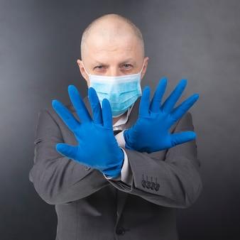 Mann in schutzhandschuhen zeigt eine medizinische gesichtsmaske. coronavirus-epidemie und persönlicher schutz für den menschen