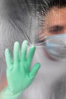 Mann in schutzmaske und handschuhen selbst isoliert in seiner wohnung während einer coronavirus-infektion