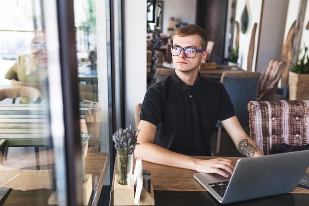 Mann in schwarz am laptop arbeiten