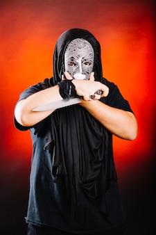 Mann in schwarz posiert mit messer