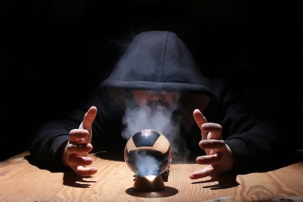 Mann in schwarzer kapuze mit kristallkugel beschwört das böse