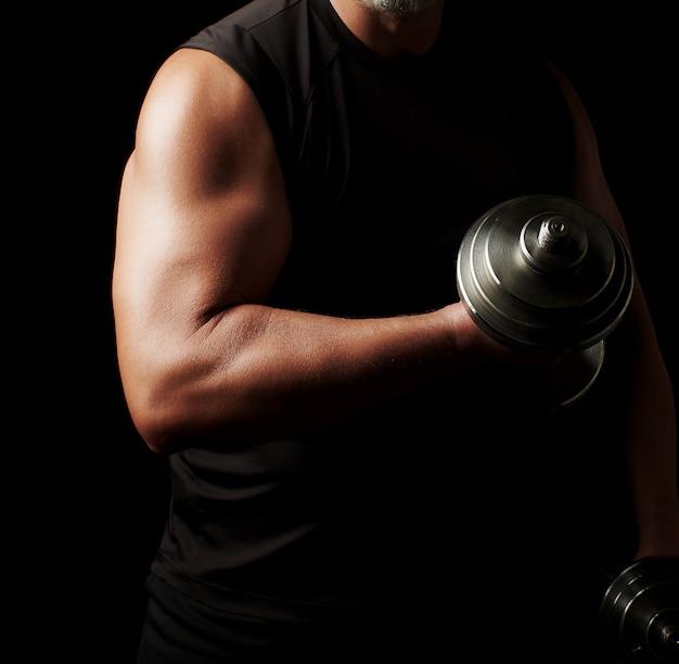 Mann in schwarzer kleidung hält stahlhanteln in seinen händen