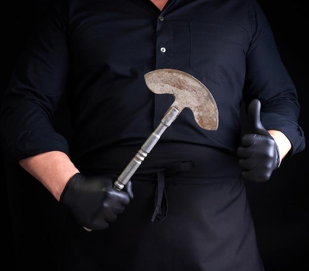 Mann in schwarzer kleidung, latexhandschuhe hält ein vintage metallaxtmesser für fleisch und gemüse