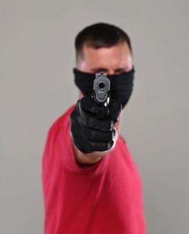 Mann in schwarzer maske mit einer waffe posiert im studio auf grauem hintergrund